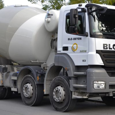 A white and grey cement mixer truck on the side of a road under a tree